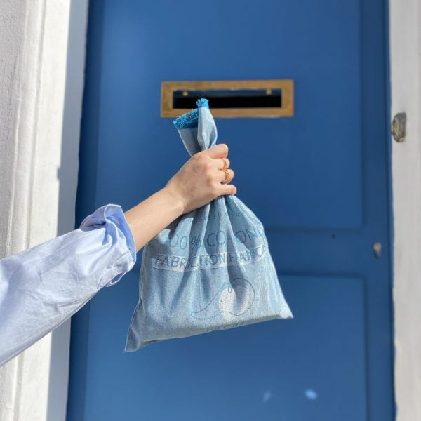 pochon upcyclé bleu paon devant porte bleuepachi main melissa fond bleu pachi